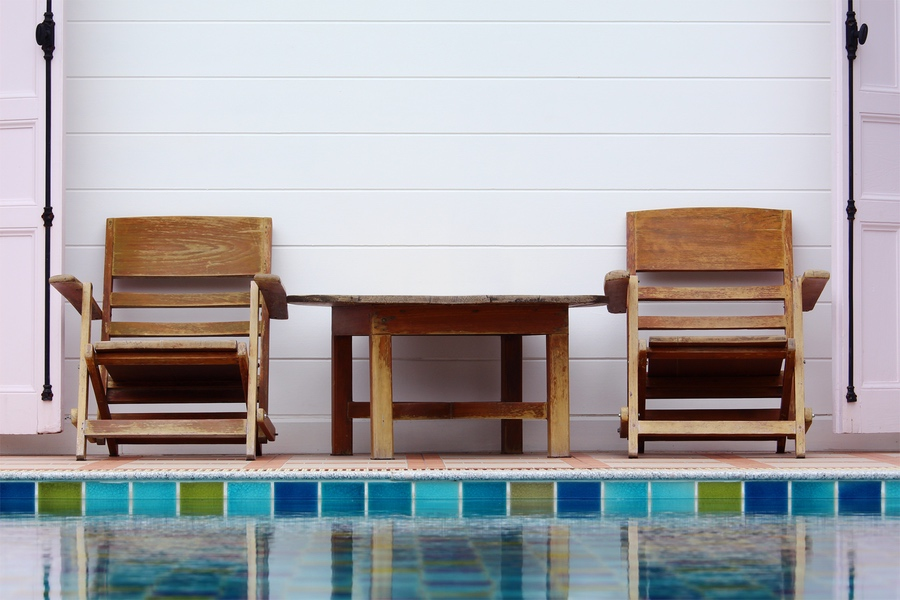 Wooden chair on ground beside swimming pool